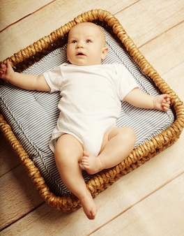 Little cute baby lying in basket