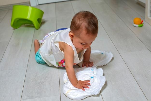 작은 귀여운 아기는 챔버 냄비 장난감을 바닥에 깨끗한 새 기저귀를 가지고 노는