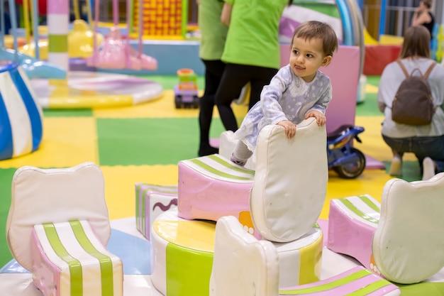 드레스를 입은 작고 귀여운 아기 소녀는 어린이 보육 놀이방에서 회전 목마를 타고 올라갑니다.