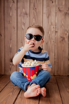 Little cute baby with 3d cinema glasses holding bucket for popcorn
