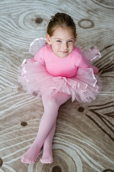 Little cute ballerina sitting on carpet