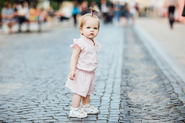 Little, cute, beautiful girl walks through the city in pink dress.