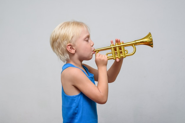 Little cute blond boy playing toy trumpet on light