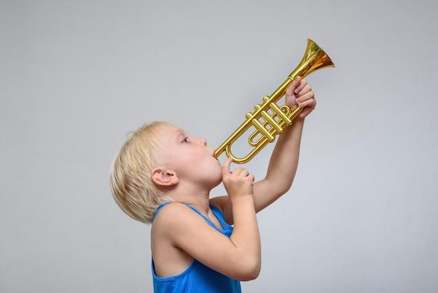 Маленький милый белокурый мальчик играет на игрушечной трубе на светлой стене