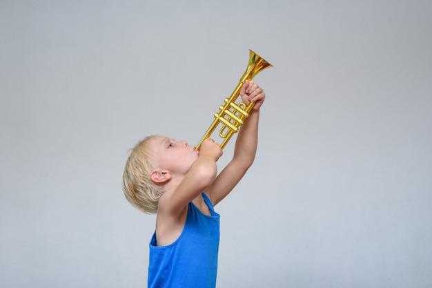 Маленький милый белокурый мальчик играет игрушку труба
