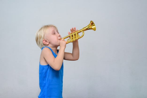 Little cute blond boy playing toy trumpet