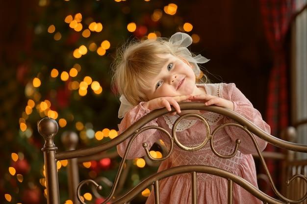 鉄のベッドのヘッドボードに立っている小さなかわいいブロンドの女の子