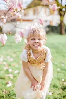 Маленькая милая блондинка 3 года играет в парке возле цветущей магнолии. весна.