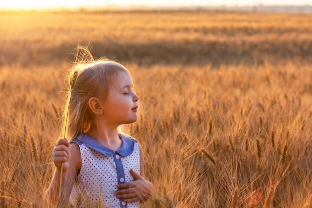Little cute blonde girl with closed eyes in the blue dress dremes and holds spikelet of wheat