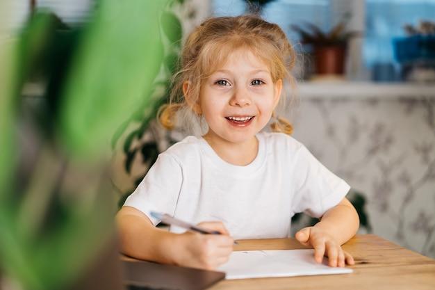 작고 귀여운 금발 소녀는 집에서 노트북 앞에서 공부하고, 온라인 학습을 하고, 학교로 돌아갑니다.