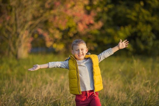 5歳の小さなかわいい男の子が秋の庭を歩きます。明るい秋の服を着た幸せな少年の肖像画。暖かく明るい秋。