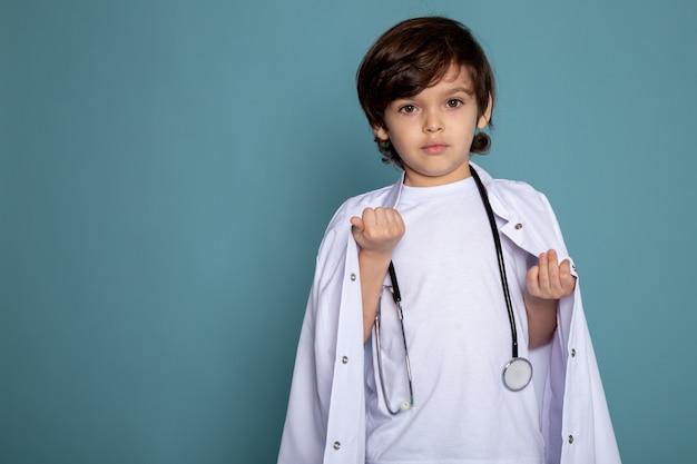 Маленький милый мальчик очаровательны сладкий в белом медицинском костюме на синем