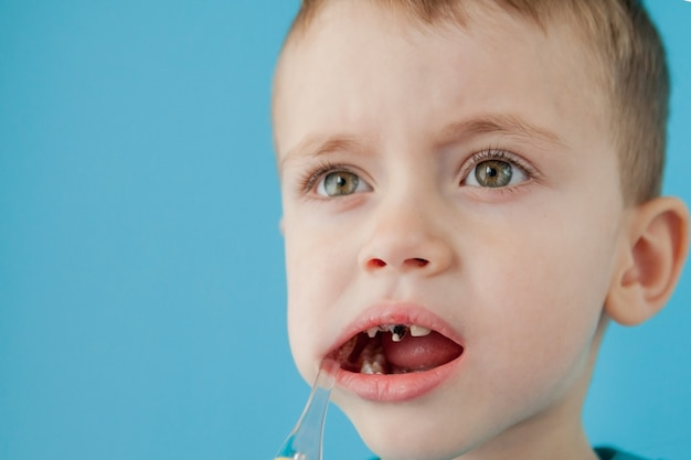 Little cute boy brushing his teeth on blue wall