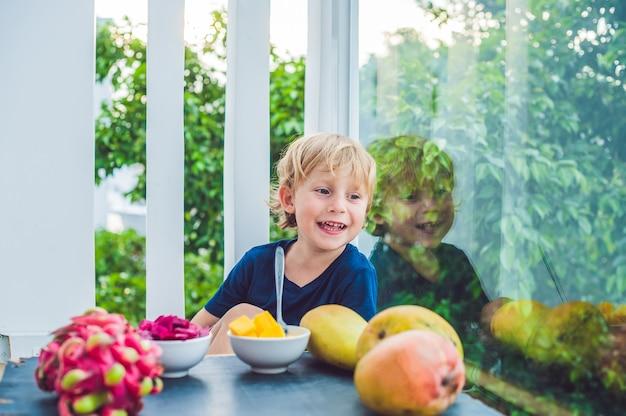 テラスでマンゴーを食べる小さなかわいい男の子。
