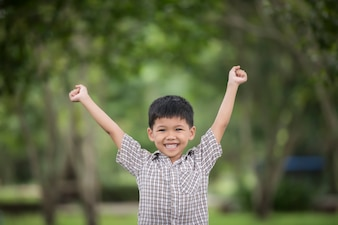 Little cute boy enjoying raising hands with nature over the blurred nature background.