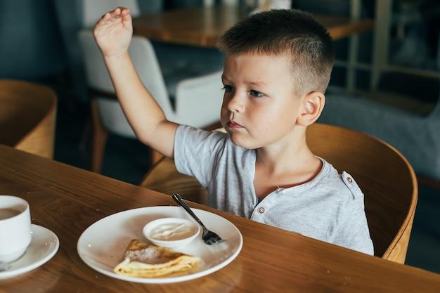 Little and cute boy having breakfast in cafe.