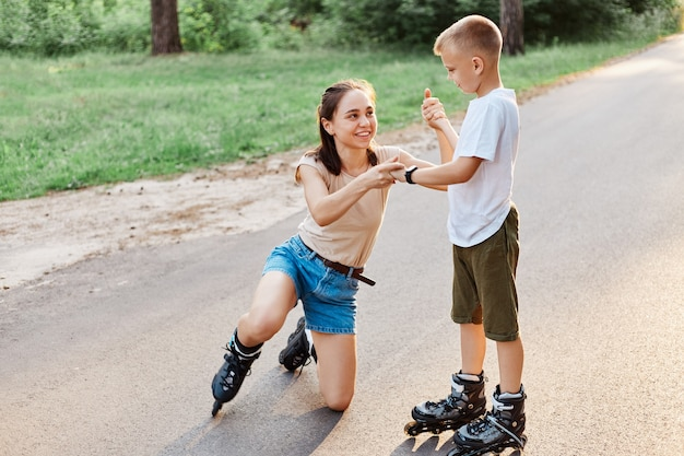 Little cute boy help mother to stand up from road after falling down in roller skates, smiling woman looking at her child, family weekend in summer park.