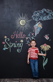Little cute boy holding flower on the chalk black board