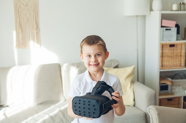 Little cute boy holds virtual reality glasses in his hands.