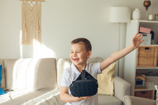 Little cute boy holds virtual reality glasses in his hands