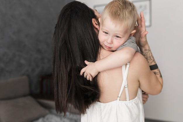 그녀의 어머니를 안고있는 귀여운 소년