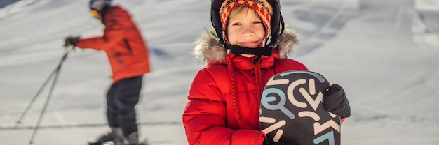 かわいい男の子はスノーボードの準備ができています。冬の子供たちのための活動。子供の冬