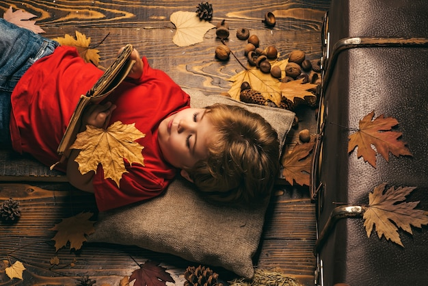 Little cute boy lies on a wooden floor with autumn leaves and read book. little child boy lies on a
