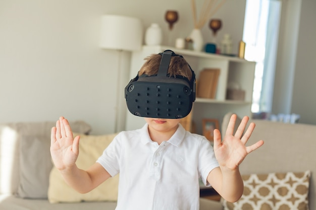Little cute boy looks at virtual reality with glasses.