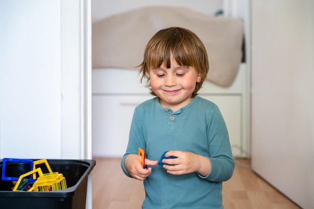 Маленький милый мальчик трех лет сидит на полу и играет с магнитными блоками