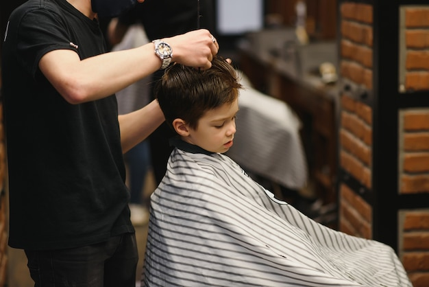 A little cute boy sits in a hairdresser's at the stylist's, a schoolchild is getting hair cut in a beauty salon, a child at a barbershop's, a short men's haircut.