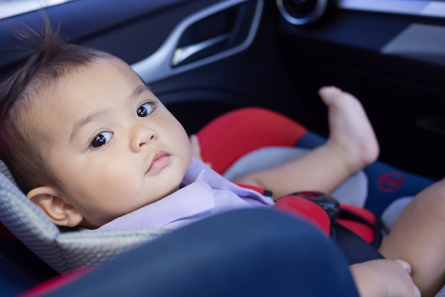Little cute boy sitting on car sit in car.