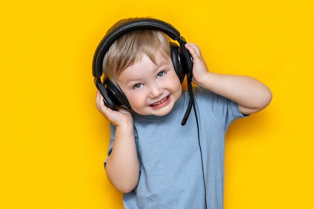 Little cute caucasian blonde boy in headphones on yellow