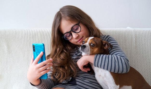 안경에 귀여운 백인 소녀는 강아지와 함께 selfie 전화를 만들
