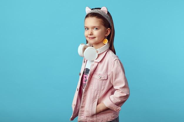 Маленькая милая кавказская девушка в розовой куртке с белыми наушниками на шее Premium Фотографии