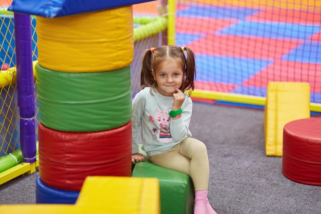 Little cute caucasian girl with funny ponytail playing with soft building blocks at indoor playground, sitting and looking directly