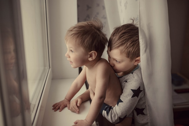 Little cute caucasian kids looking out the window a boy kissing shoulder of his little brother
