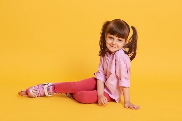 Little cute caucasian woman with roller skates on floor