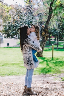 Little cute child baby girl kiss on cheek and hug embrace with happy pretty woman in green park