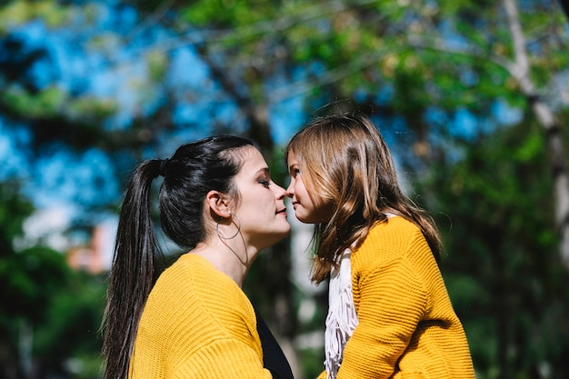 Little cute child baby girl kiss on nose and hug embrace with happy pretty woman in green park