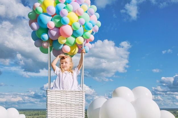 푸른 하늘에 풍선 비행선을 타고 푸른 잔디에서 아름답고 행복한 어린 소녀