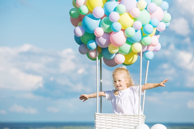 Little cute child girl beautiful and happy on green grass with balloon airship on blue sky
