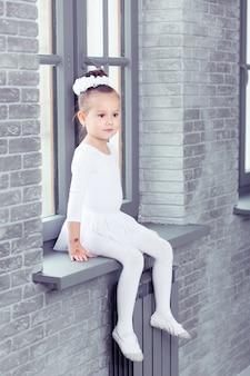 モダンダンススタジオの窓に座っている白いダンスの形で小さなかわいい子供の女の子