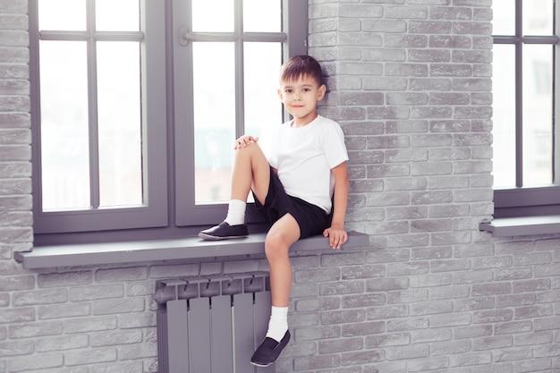 Маленькая милая детская девочка в форме белого танца, сидя на окне в студии современного танца