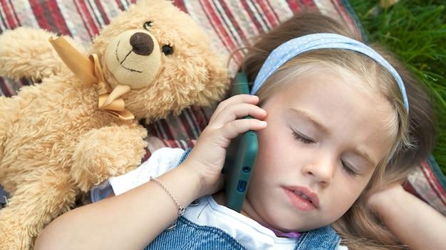 彼女のテディベアのおもちゃが携帯電話で話している夏の屋外で緑の芝生の毛布の上に横たわっている小さなかわいい子供の女の子。