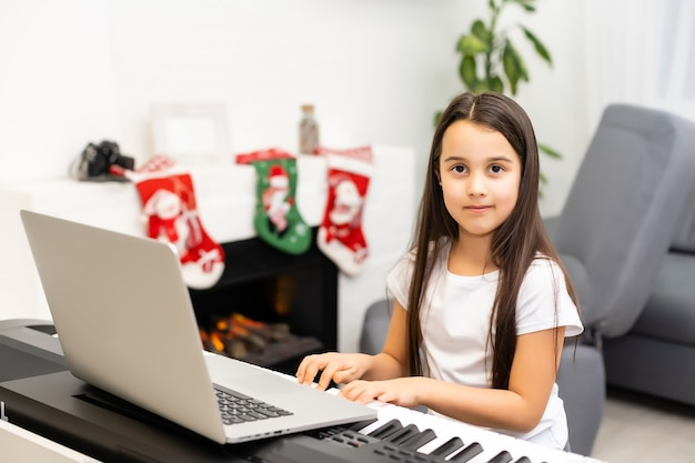 Little cute child girl playing the piano with decorated christmas