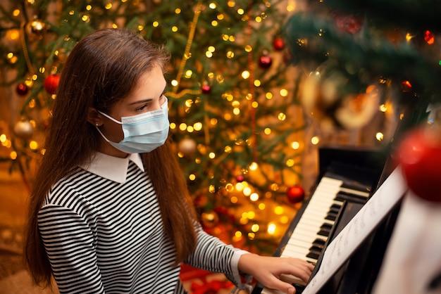 얼굴 보호 마스크에 피아노를 연주 작은 귀여운 아이 소녀