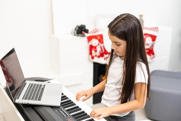 飾られたクリスマスとピアノを弾く小さなかわいい子供の女の子