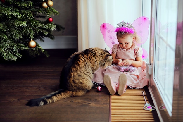 Little cute child with big cat playing together near christmas tree.