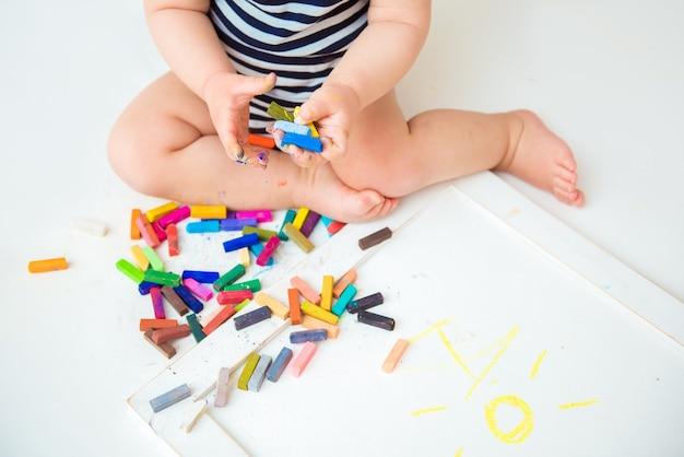 Маленький милый ребенок с творчеством рисует мелками дома на листе белой бумаги. концепция раннего развития творческих способностей детей