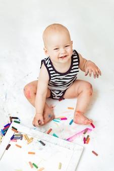 창의력을 가진 작은 귀여운 아이가 집에서 크레용으로 흰 종이에 그립니다.